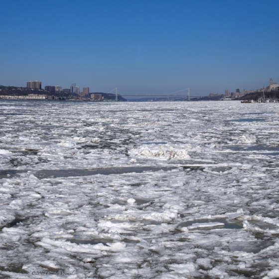 The Hudson River covered in ice with a view of the George Washington Bridge